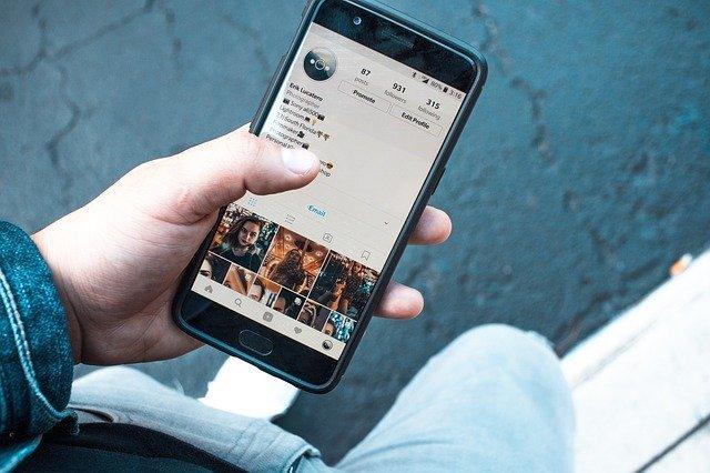 osoba s uchopeným mobilním telefonem v ruce